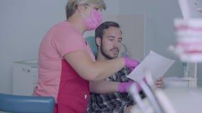 Dentista de sexo femenino en máscara rosada y guantes que muestran a la imagen paciente masculina de sus dientes en la pantalla E almacen de metraje de vídeo