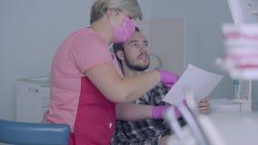 Dentista de sexo femenino en máscara rosada y guantes que muestran a la imagen paciente masculina de sus dientes en la pantalla E almacen de video