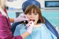 Dentista de sexo femenino en oficina dental que habla con el paciente femenino y que se prepara para el tratamiento Embroma la es imagen de archivo libre de regalías