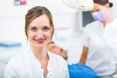 Dentista de sexo femenino experimentado en su cirugía Foto de archivo