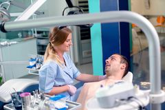 Dentista de sexo femenino joven que habla con su paciente en la oficina del dentista fotos de archivo
