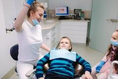 Dentista de sexo femenino de la ayuda de la ni?a, nuevo tratamiento del examinationand de los dientes de cavidades fotografía de archivo libre de regalías