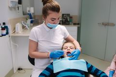 Dentista de sexo femenino de la ayuda de la ni?a, nuevo tratamiento del examinationand de los dientes de cavidades fotos de archivo libres de regalías