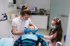 Dentista de sexo femenino de la ayuda de la ni?a, nuevo tratamiento del examinationand de los dientes de cavidades imagenes de archivo