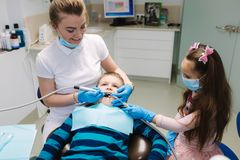 Dentista de sexo femenino de la ayuda de la ni?a, nuevo tratamiento del examinationand de los dientes de cavidades foto de archivo libre de regalías