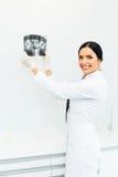 Dentista de sexo femenino Looking en la radiografía dental en clínica Foto de archivo
