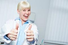 Dentista de sexo femenino que anima que detiene sus pulgares Imagen de archivo libre de regalías