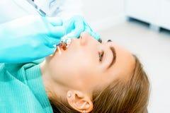 Dentista de sexo femenino que comprueba encima de los dientes pacientes con los apoyos en la oficina dental de la clínica Medicin imagenes de archivo