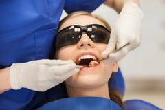 Dentista de sexo femenino que comprueba los dientes pacientes de la muchacha Fotografía de archivo libre de regalías