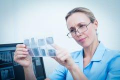 Dentista de sexo femenino que mira la radiografía Imagenes de archivo