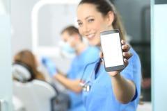 Dentista de sexo femenino que muestra la pantalla del teléfono imágenes de archivo libres de regalías