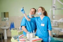 Dentista de sexo femenino que muestra la radiografía al colega masculino en la clínica dental imagen de archivo
