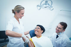 Dentista de sexo femenino que sacude las manos con la mujer imagen de archivo