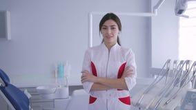 Dentista de sexo femenino que se coloca y que sonríe a la cámara con los brazos cruzados almacen de video