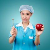 Dentista de sexo femenino que sostiene una manzana y las herramientas del equipamiento médico del metal Imágenes de archivo libres de regalías