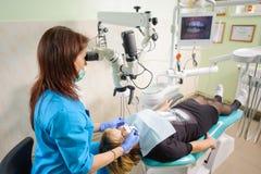 Dentista de sexo femenino que trabaja con el microscopio en la clínica moderna del dentista Fotografía de archivo libre de regalías