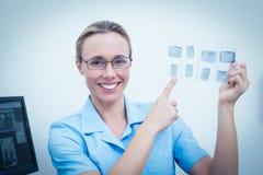 Dentista de sexo femenino sonriente que señala en la radiografía Imagenes de archivo
