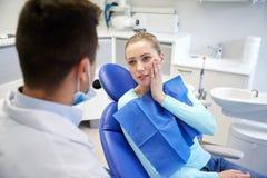Dentista de sexo masculino con el paciente de la mujer en la clínica Imagenes de archivo