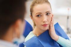 Dentista de sexo masculino con el paciente de la mujer en la clínica Imagen de archivo libre de regalías