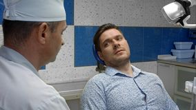 Dentista de sexo masculino con la discusión del problema del paciente masculino en la clínica Imagen de archivo libre de regalías