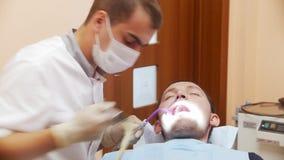 Dentista de sexo masculino en curso de tratar los dientes pacientes del ` un s del varón En la recepción en el dentista en la clí metrajes