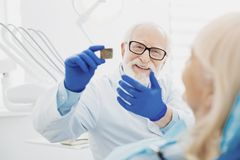 Dentista de sexo masculino optimista que da la explicación fotos de archivo