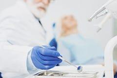 Dentista de sexo masculino profesional que toma el espejo dental foto de archivo libre de regalías