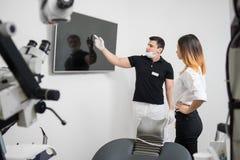 Dentista de sexo masculino que muestra al paciente femenino su imagen dental de la radiografía en la pantalla de ordenador en una Foto de archivo