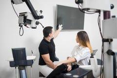 Dentista de sexo masculino que muestra al paciente femenino su imagen dental de la radiografía en la pantalla de ordenador en una Fotografía de archivo