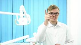 Dentista de sexo masculino serio en la capa blanca que señala el finger a usted y que sacude la cabeza en la oficina dental de la almacen de metraje de vídeo