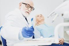 Dentista de sexo masculino tranquilo que pone detrás el espejo dental imagen de archivo
