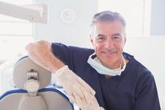 Dentista de sorriso que inclina-se contra a cadeira dos dentistas fotografia de stock royalty free