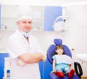 Dentista del ritratto con il paziente nei precedenti esaminando è venuto Fotografia Stock Libera da Diritti