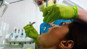 Dentista della donna che cura i denti delle signore, medico che fornisce i servizi dentari, medicina fotografie stock