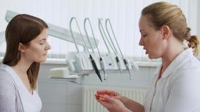 Dentista della donna che parla con il paziente femminile in clinica Medico professionista femminile sul lavoro Assegno dentale in video d archivio