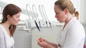Dentista della donna che parla con il paziente femminile in clinica Medico professionista femminile sul lavoro Assegno dentale in stock footage