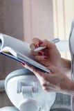 Dentista With della donna un taccuino e una penna contro i precedenti o Immagine Stock Libera da Diritti