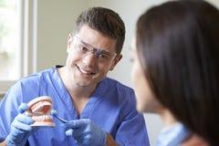 Dentista Demonstrating Correct Use del cepillo de dientes al cliente femenino imagen de archivo libre de regalías