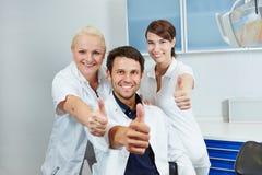 Dentista e equipe dental que mantêm os polegares Imagem de Stock Royalty Free