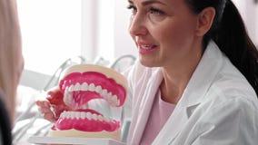 Dentista e paciente que fazem uma conversação durante a verificação acima filme