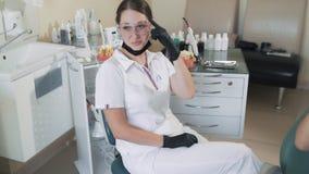 Dentista e risata e sorriso pazienti della donna in clinica dentaria, movimento lento Video divertente stock footage
