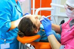 Dentista e seus dentes assistentes das brocas do paciente fotografia de stock