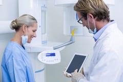 Dentista ed assistente dentario che lavorano alla compressa digitale Fotografia Stock