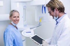 Dentista ed assistente dentario che lavorano alla compressa digitale Immagine Stock