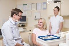 Dentista ed assistente nella stanza dell'esame con la donna fotografia stock