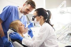 Dentista ed il suo assistente che fanno il loro lavoro nella clinica del dentista fotografia stock libera da diritti