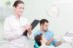 Dentista ed il suo assistente sul lavoro Immagine Stock