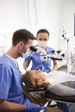 Dentista ed il suo funzionamento di aiuto con il microscopio dentario immagini stock libere da diritti