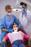 Dentista ed infermiere che esaminano un giovane paziente con gli strumenti Fotografia Stock