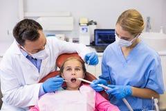 Dentista ed infermiere che esaminano un giovane paziente con gli strumenti Fotografie Stock